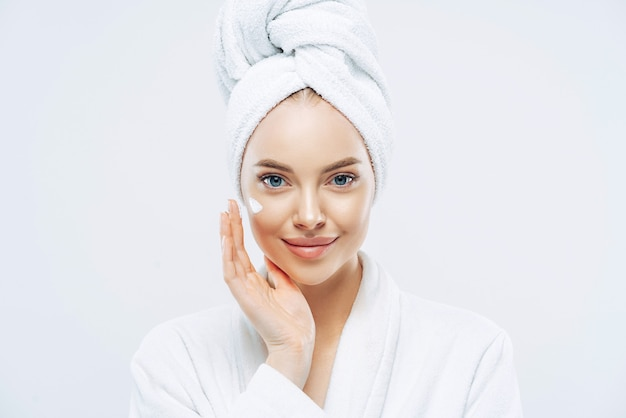 Young confident caucasian woman applies face cream enjoys cosmetic product
