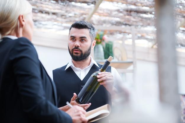 Молодой уверенный кавист с бутылкой вина разговаривает со своим коллегой во время обсуждения ее характеристик на работе