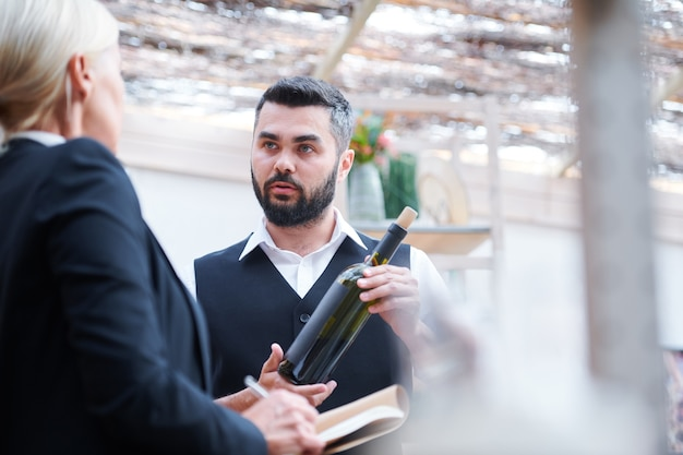 Young confident cavist with bottle of wine talking to his colleague during discussion of its characteristics at work