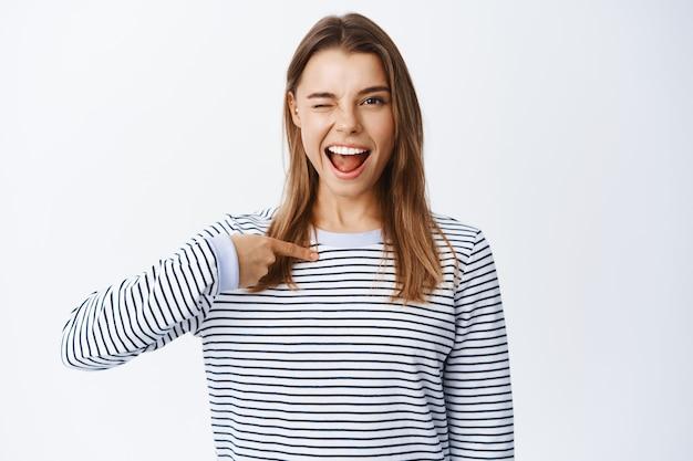 Giovane donna sicura e sfacciata che strizza l'occhio davanti, indicando se stessa e sorridendo determinata, autopromozione di risultati e abilità personali, muro bianco