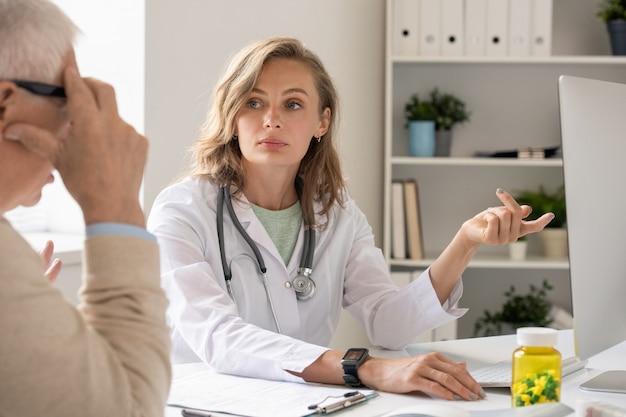 Молодой уверенный в себе врач в белом халате, указывая на экран компьютера, консультируясь со старшим пациентом и делая презентацию нового лекарства