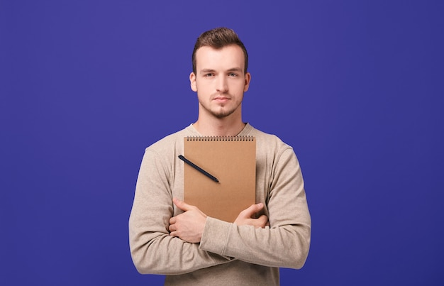 Young confident confident guy hugging brown notebook with black ballpoint pen by hands