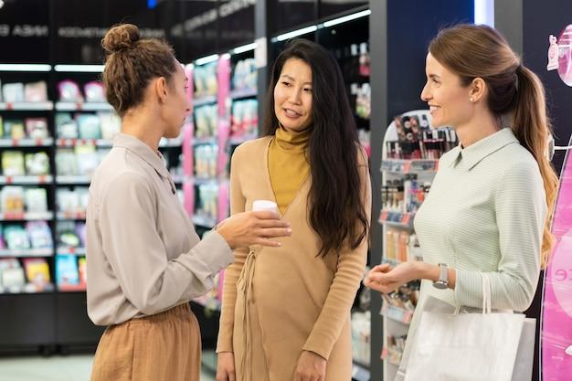 異文化間の女性のクライアントにフェイシャルクリームをテストするように提案しながら、それを推奨する美容スーパーマーケットの若い自信のあるコンサルタント