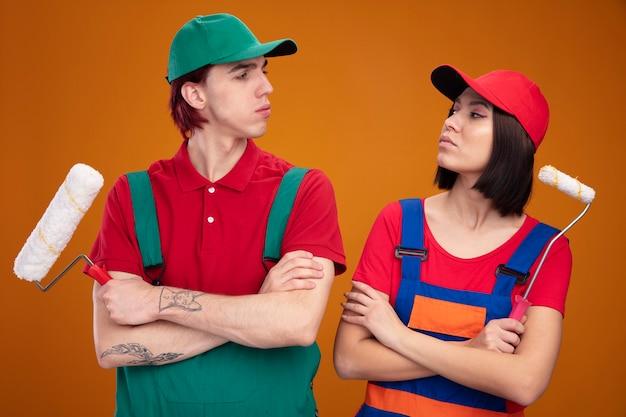 건설 노동자 유니폼을 입은 젊은 자신감 있는 부부와 닫힌 자세로 서 있는 모자는 주황색 벽에 격리된 서로를 바라보는 페인트 롤러를 들고 있습니다.