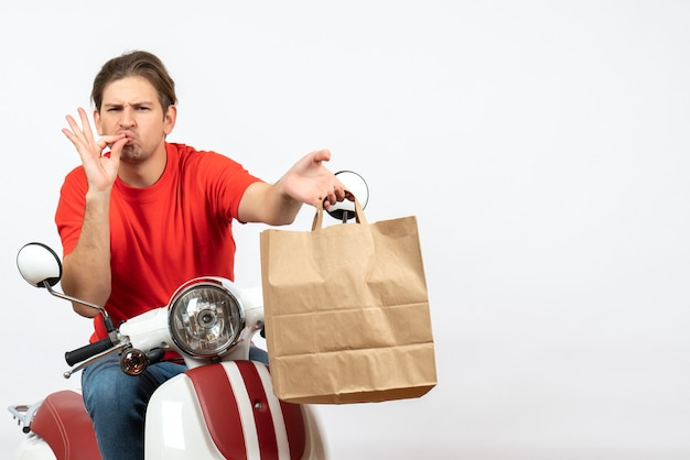 Young confident courier guy in red uniform sitting on scooter giving paper bag making perfect gesture on white wall