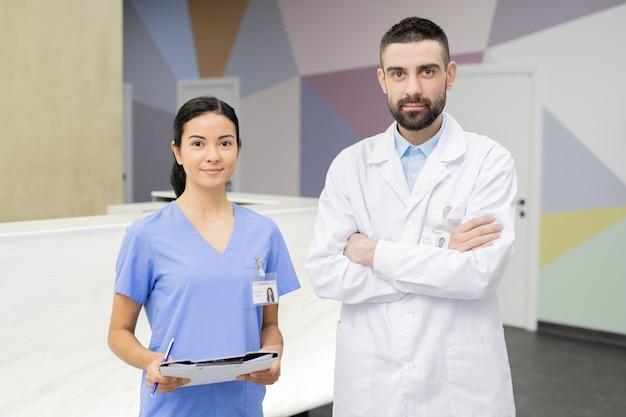 Молодой уверенный в себе врач со скрещенными руками в белом халате и его симпатичная помощница стоят в холле стоматологической клиники у стойки регистрации
