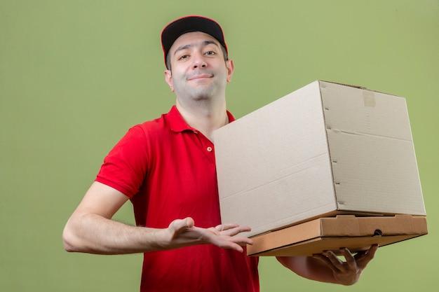 Молодой уверенно доставщик в красной форме, держа картонные коробки с улыбкой на лице над зеленой стеной