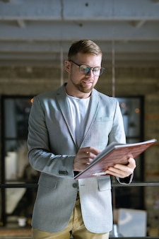 Young confident designer in formalwear looking at cover of fashion magazine while going to look it through
