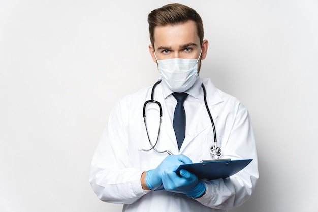 Young and confident doctor is holding the clipboard with a documents