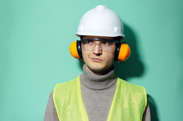 アクアメンテカラーの壁に安全装置を身に着けている若い自信のあるエンジニア。