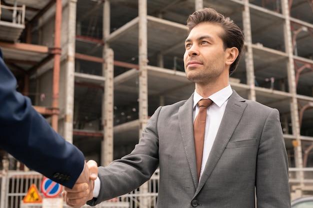 자신의 파트너 또는 고객을 건물 사이트로 환영하는 정장을 입은 젊은 자신감 사업가 또는 계약자