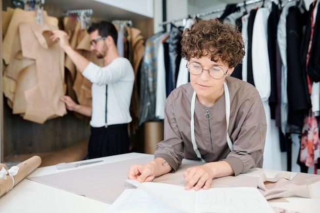 職場で新しいモデルに取り組んでいる間紙にスケッチを見て自信を持って若いファッション・デザイナー