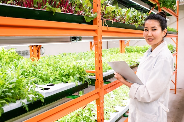 Young confident female biologist making notes in document while studying new sorts of horticultural plants in greenhouse