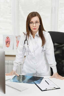 Young confident female doctor standing at desk, holding x-ray of lungs, fluorography, roentgen in light office in hospital