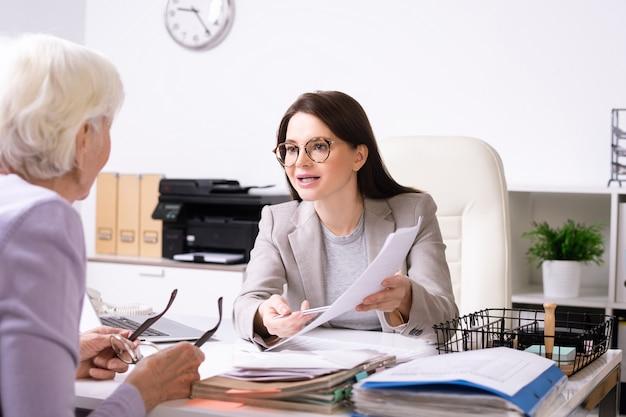 シニアクライアントにオフィスで彼女の前に座って紙に記入する方法を説明する若い自信のある女性保険代理店
