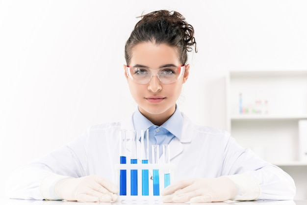 Young confident female laboratory worker in protective eyeglasses and gloves working with liquid substances in flasks