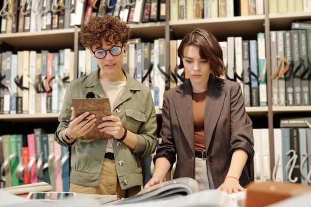 젊고 자신감 있는 여성 상점 조수는 새 월페이퍼의 색상과 질감에 대해 상담하고 적합한 샘플을 선택하는 데 도움을 줍니다.