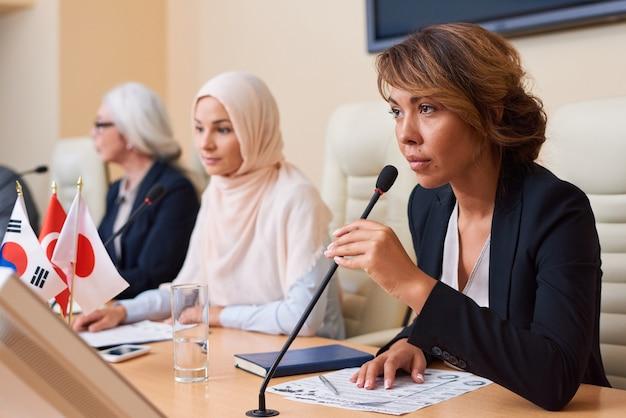 Молодая уверенная в себе женщина-спикер в строгой одежде держит микрофон у рта, собираясь ответить или задать вопрос на конференции