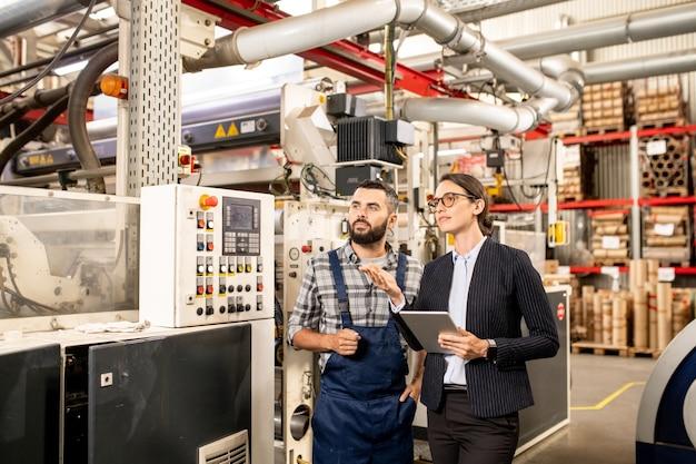 タブレットと近代的な工場のテストのエンジニアと石油化学製品を処理する新しいシステムまたは技術について話している若い自信を持って女性