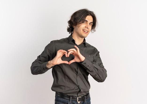 Giovane uomo caucasico bello fiducioso gesti il segno della mano del cuore isolato su priorità bassa bianca con lo spazio della copia