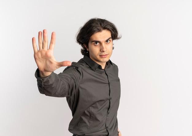 Молодой уверенный в себе красивый кавказский мужчина жестами останавливает знак рукой на белом фоне с копией пространства