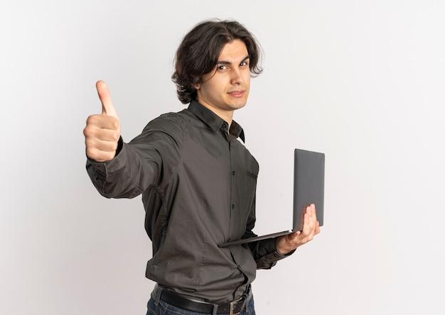 Il giovane uomo caucasico bello sicuro tiene il computer portatile e il pollice in alto isolato su priorità bassa bianca con lo spazio della copia