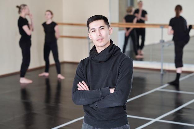 ポーズをとりながら胸で腕を組む現代のバレエダンスコースの若い自信のあるインストラクター