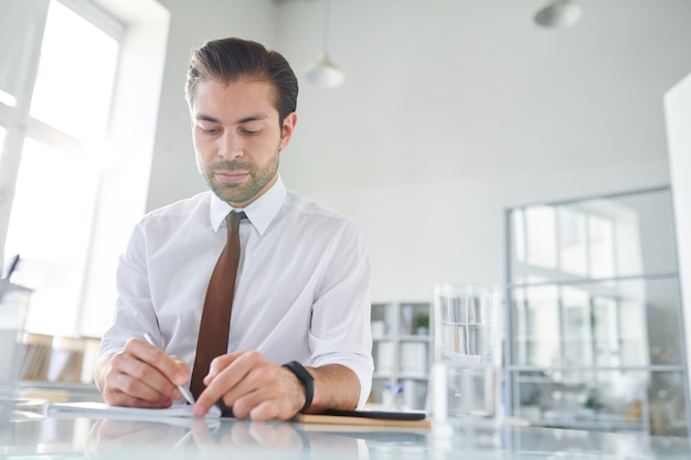 Young confident lawyer making working notes on paper while sitting by desk in office