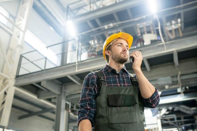 현대 공장의 대형 작업장에 서 있는 동안 워키토키를 사용하여 보호용 헬멧과 작업복을 입은 젊은 자신감 있는 남성 엔지니어