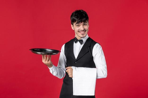 Giovane cameriere maschio fiducioso in uniforme con farfalla sul collo che tiene vassoio e asciugamano su sfondo rosso