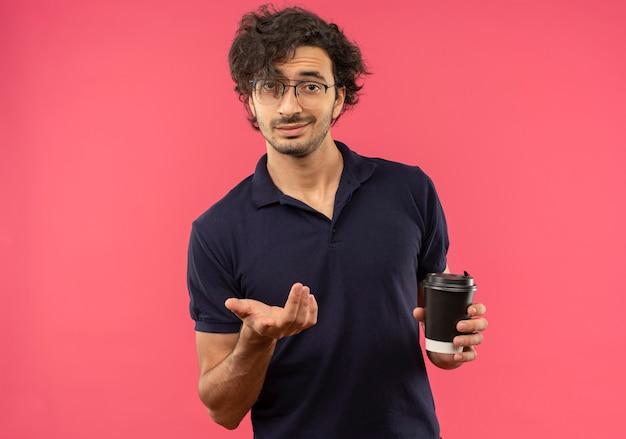 Il giovane uomo sicuro in camicia nera con vetri ottici tiene la tazza di caffè e punti isolati sulla parete rosa
