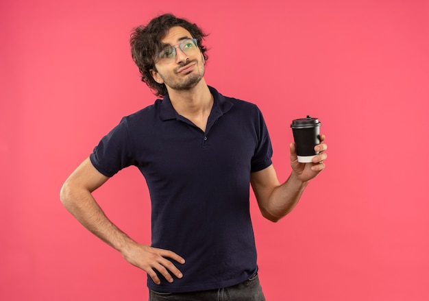 Young confident man in black shirt with optical glasses holds coffee cup and puts hand on waist isolated on pink wall