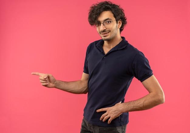 Giovane uomo fiducioso in camicia nera con occhiali ottici punta a lato e sembra isolato sulla parete rosa