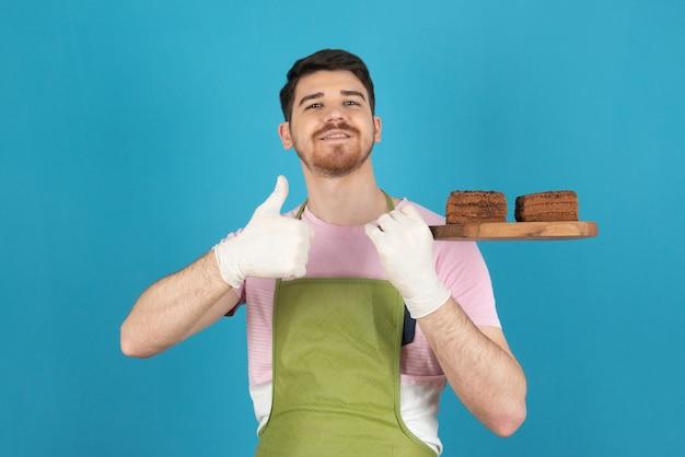 青で新鮮な自家製ケーキのスライスを保持している自信を持って若い男。