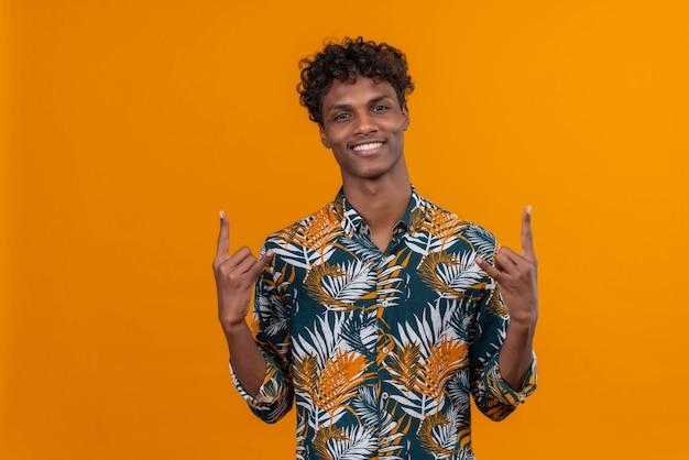 Giovane uomo fiducioso che tiene le mani in un gesto di appassionato di musica rock per esprimere l'emozione di successo su uno sfondo arancione