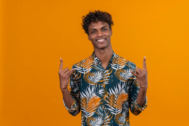 Молодой уверенный в себе мужчина, взявшись за руки в жесте поклонника рок-музыки, чтобы выразить эмоции успеха на оранжевом фоне