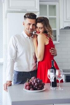 자신감이 젊은이 빨간 드레스에 그의 여자 친구를 포옹