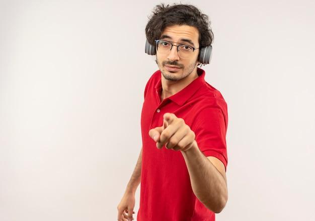 光学ガラスと白い壁に分離されたヘッドフォンポイントを持つ赤いシャツの若い自信を持って男