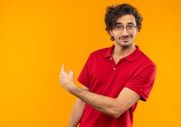 光学メガネと赤いシャツを着た若い自信のある男は後ろを指し、オレンジ色の壁に孤立して見える
