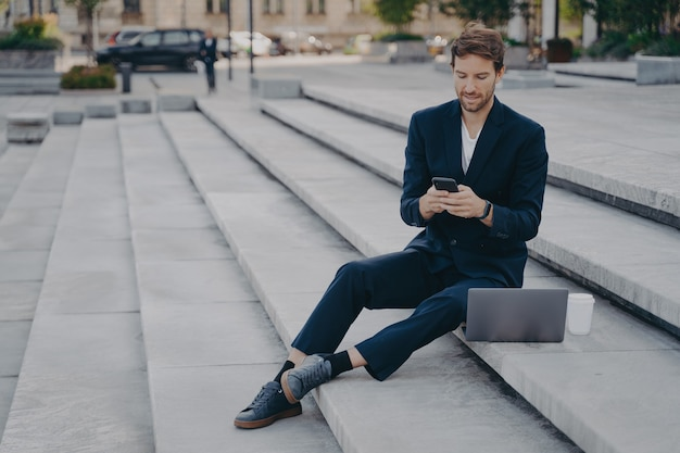 Молодой уверенный в себе мужчина в стильном костюме с помощью смартфона, сидя на ступеньках снаружи с ноутбуком