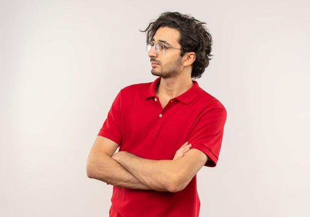 Giovane uomo fiducioso in camicia rossa con vetri ottici incrocia le braccia e guarda il lato isolato sul muro bianco