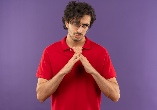Young confident man in red shirt with optical glasses holds hands together and looks at side isolated on violet wall