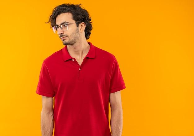 Giovane uomo fiducioso in camicia rossa con vetri ottici guarda al lato isolato sulla parete arancione
