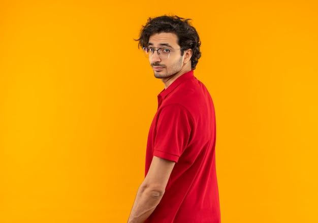 Giovane uomo fiducioso in camicia rossa con vetri ottici sta con la schiena e sembra isolato sulla parete arancione