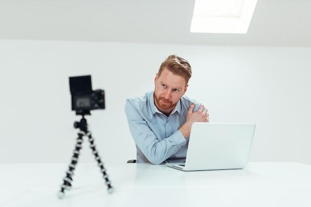 Young confident man speaker talking on digital camera recording vlog sitting at desk with laptop.