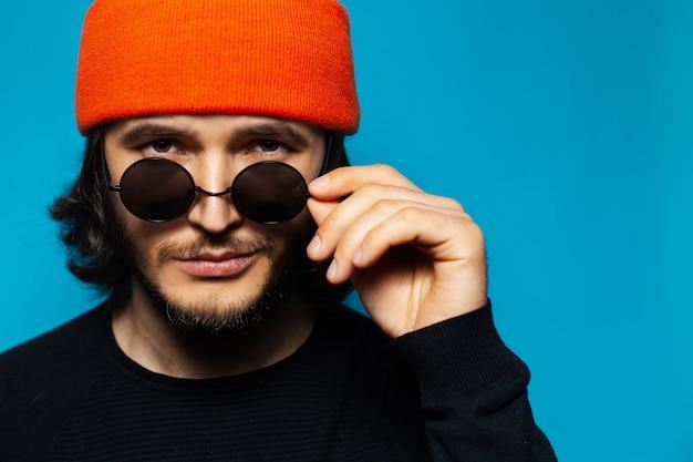 Молодой уверенный в себе мужчина в круглых очках и оранжевой шапочке на синем фоне
