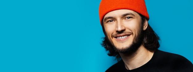 Молодой уверенный в себе мужчина с оранжевым бени на синем фоне