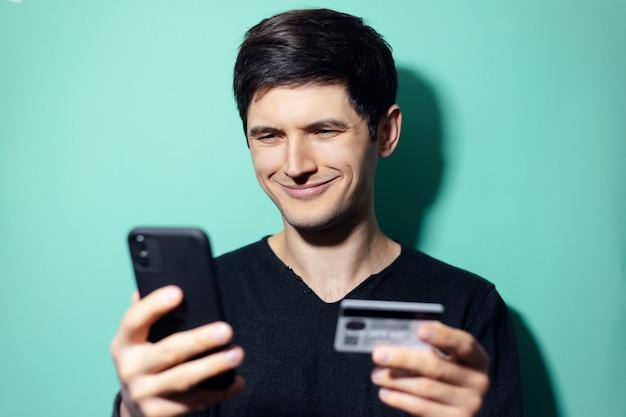 アクアメンテ色の壁にスマートフォンとクレジットカードを手に自信を持って若い男。