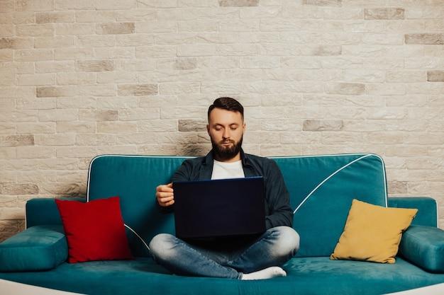 자신감이 젊은이 가정에서 일하고, 그의 소파에 앉아.