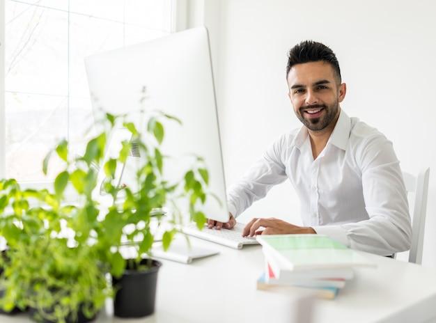 Молодой уверенно человек, работающий в современном офисе, полный света